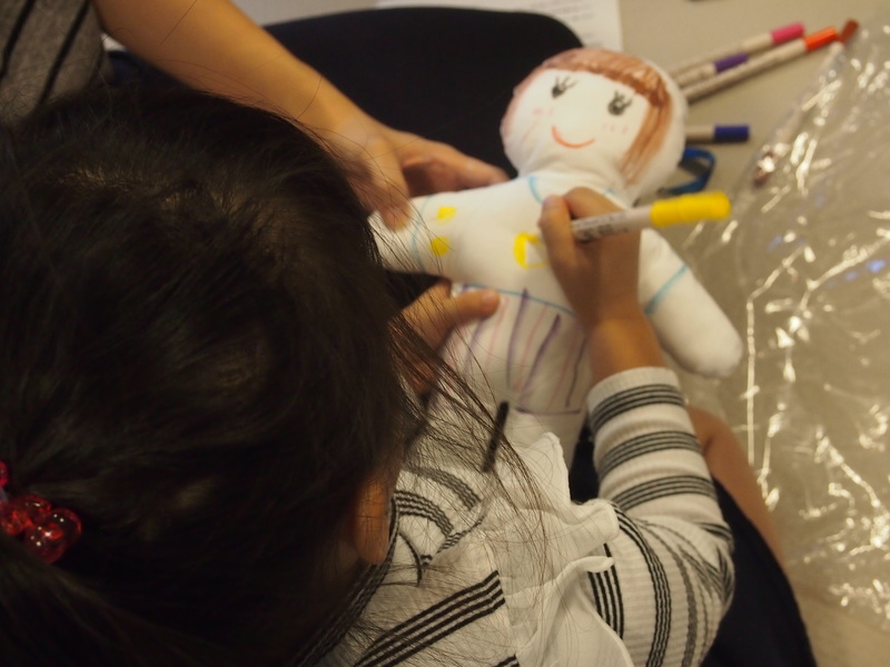A child draws a face and clothes on a doll.
